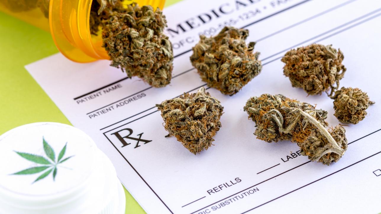 Medical marijuana buds spilling out of prescription bottle with branded lid onto blank medical prescription pad on green background
