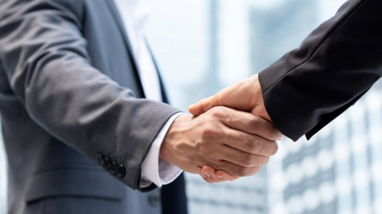 Businessmen making handshake outdoors in city office building background for merger and acquisition concept